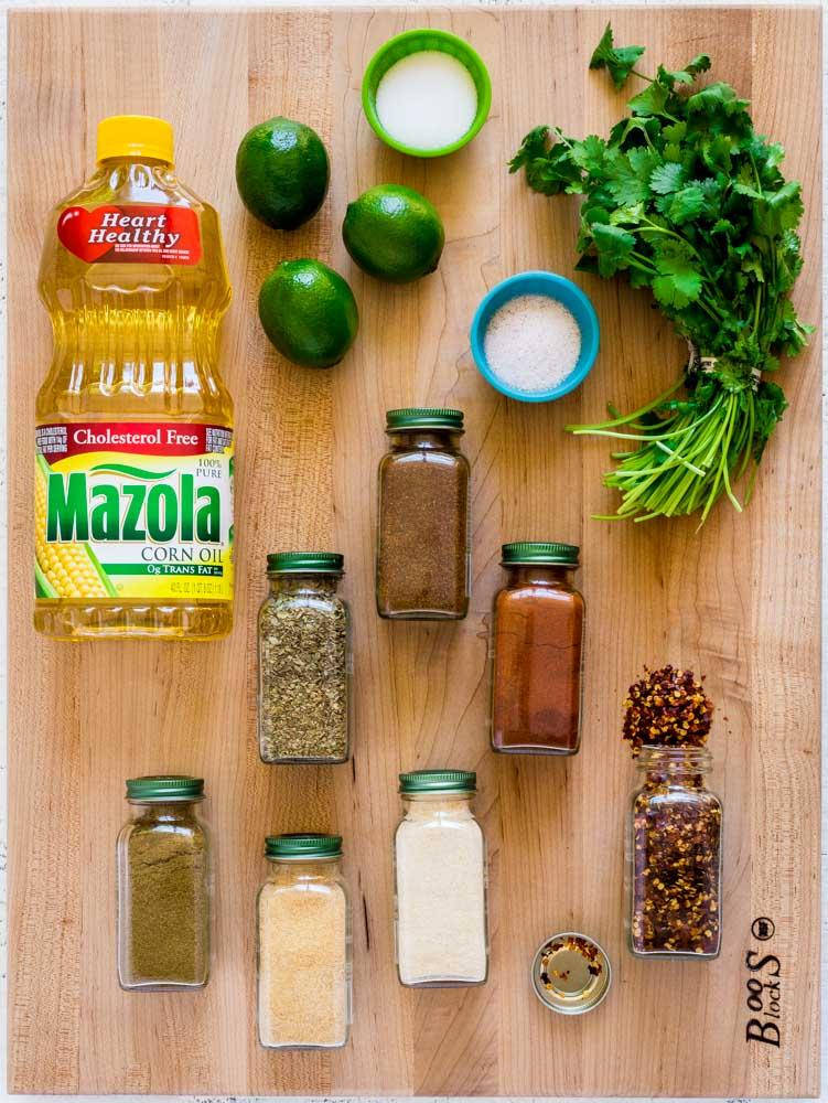 Steak fajita marinade ingredients laid out on a maple wood board