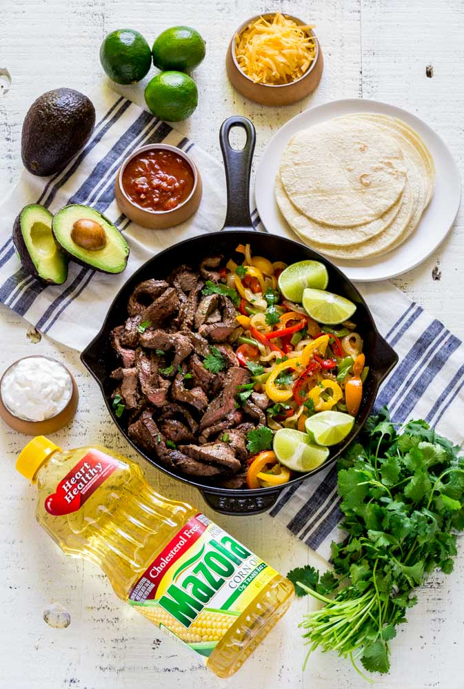 Steak fajitas in a black cast-iron pan with colorful grilled veggies.