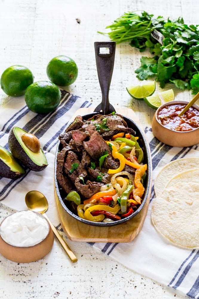 A sizzling platter of steak fajitas served with corn tortillas, avocado, sour cream and salsa.