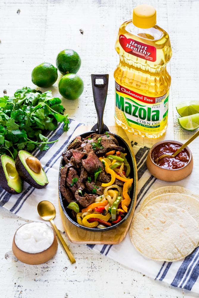 Beef Fajitas served on a sizzling cast-iron platter set on a wooden base.