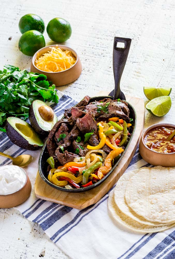 An individual serving of sizzling steak fajitas on a cast-iron platter with wooden base.