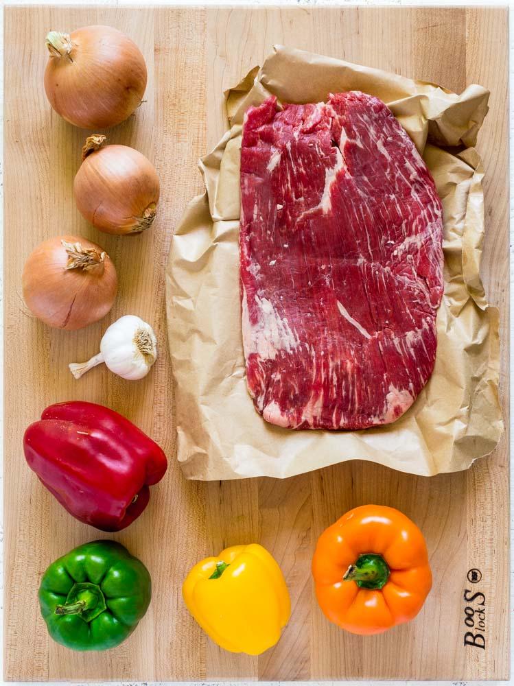 Steak fajita recipe ingredients on a wooden board: flank steak, yellow onions, garlic, colorful bell peppers.