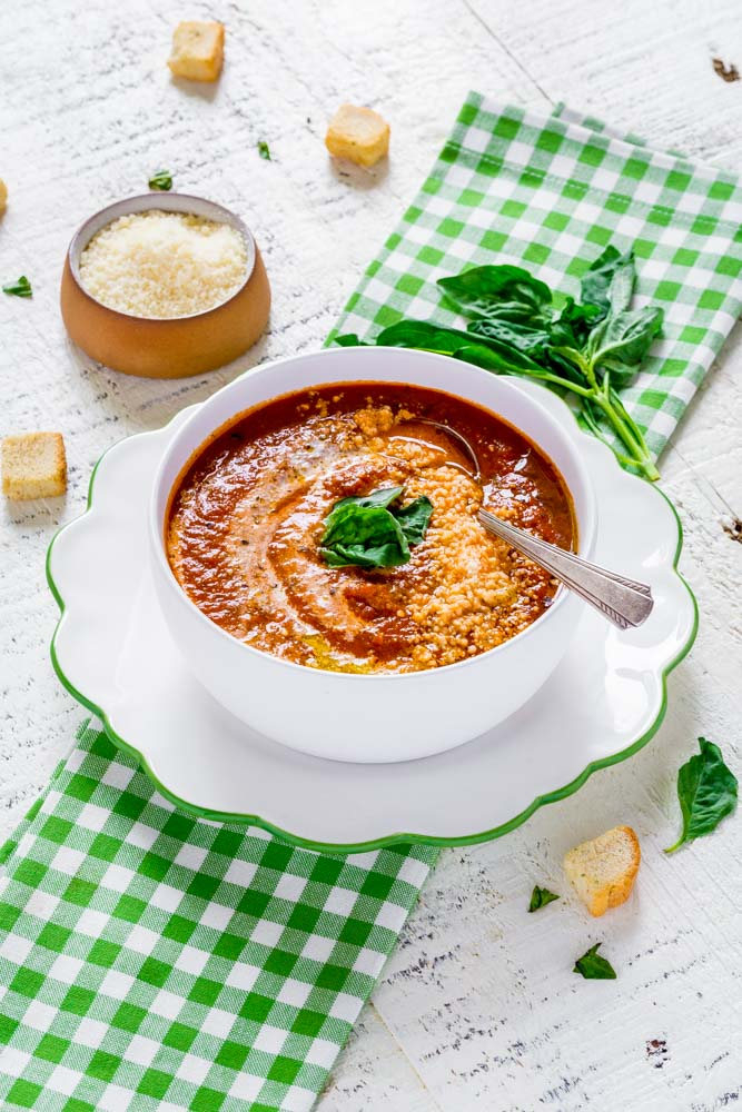 Best tomato soup recipe served in white bowl and garnished with fresh basil and parmesan cheese.