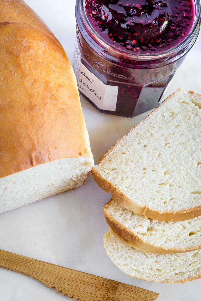 Homemade loaf of bread, with 3 freshly-sliced pieces, next to a jar of berry preserves.