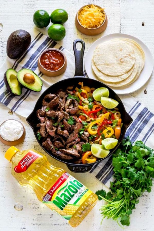 Steak fajitas in a black cast-iron skillet surrounded by fresh flavorful garnishes and corn tortillas.