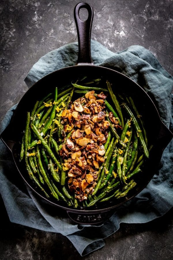 Classic Green Beans Almondine presented in a black cast-iron skillet.