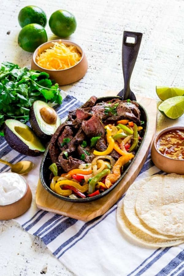 Pinterest graphic for easy steak fajitas served in a sizzling cast-iron platter with veggies.