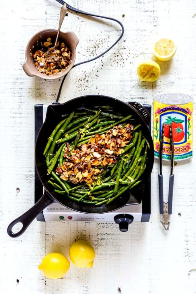 Garnishing sautéed French green beans with lemon juice, lemon zest, and almondine.