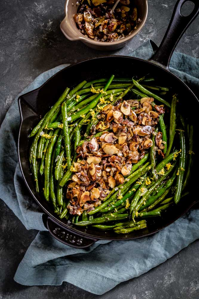 String Beans Almondine served in a black cast-iron skillet alongside a ramekin of almondine.