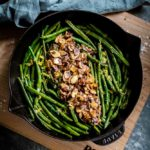Green Beans Almondine served in a black skillet seated on a wooden maple board.