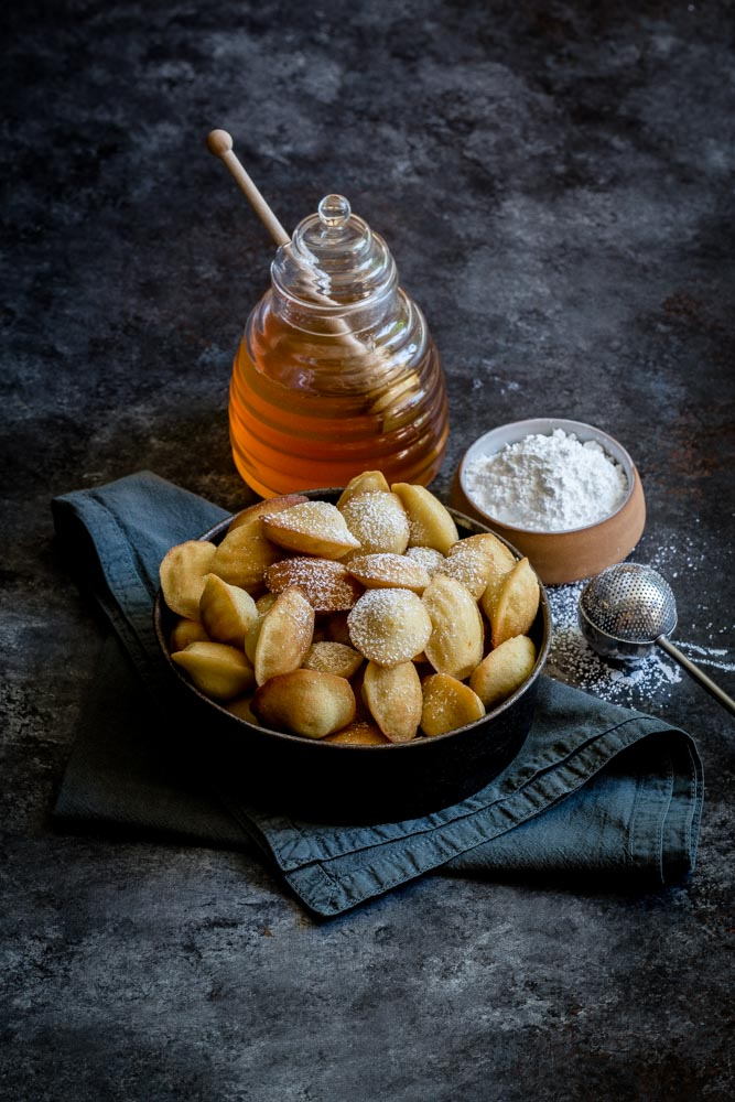 French Madeleine Cookies in a round serving dish with honey and powdered sugar in the background.