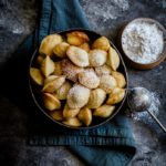 French Madeleine Cookies in a black serving bowl with a metal wand of powdered sugar.