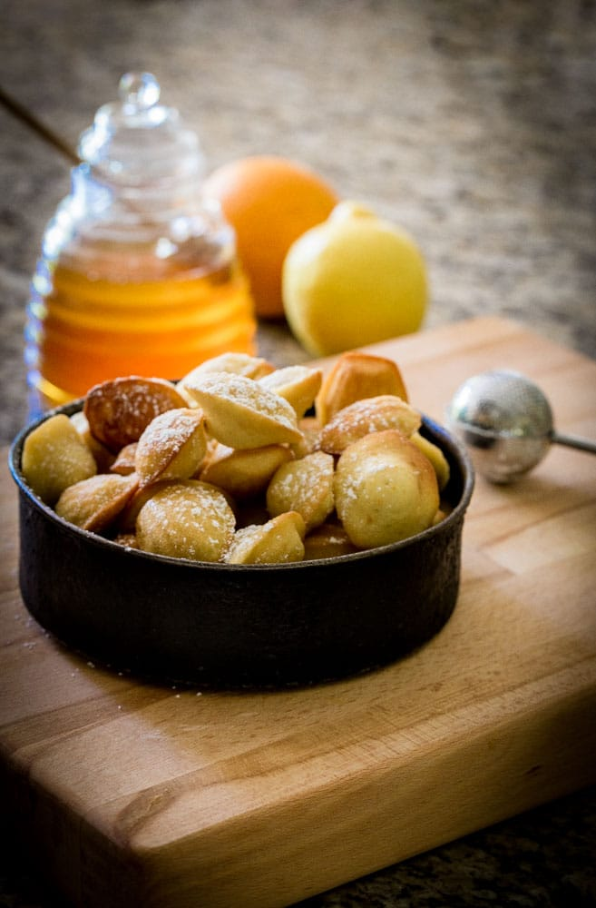 Freshly baked Madeleines in a small black serving dish on a maple wood board.