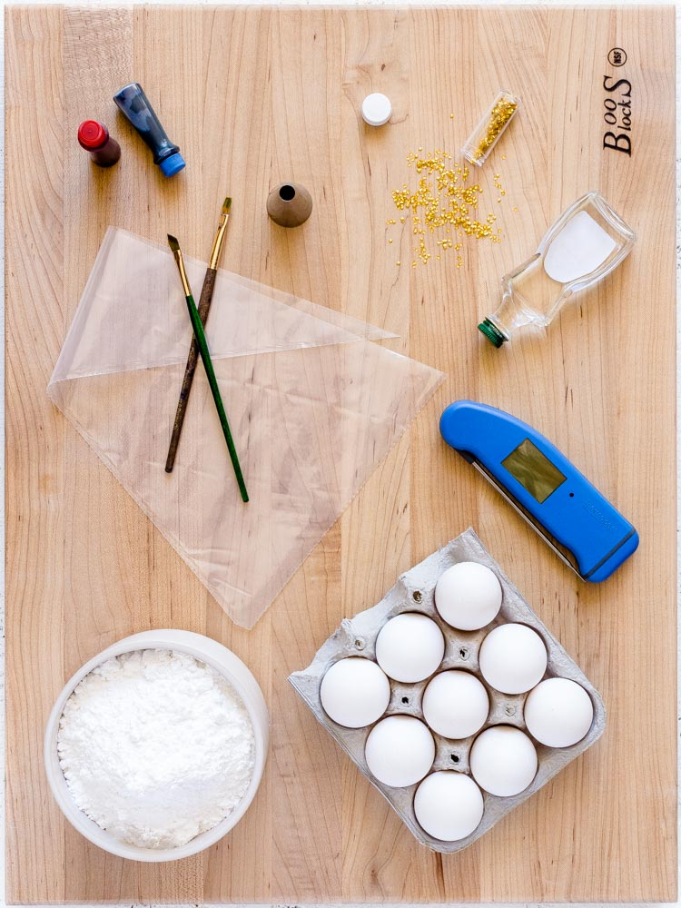 Ingredients for making meringue cookies laid out on a wooden board.