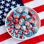 A plate of 4th of July meringue cookies on an American flag tablecloth.
