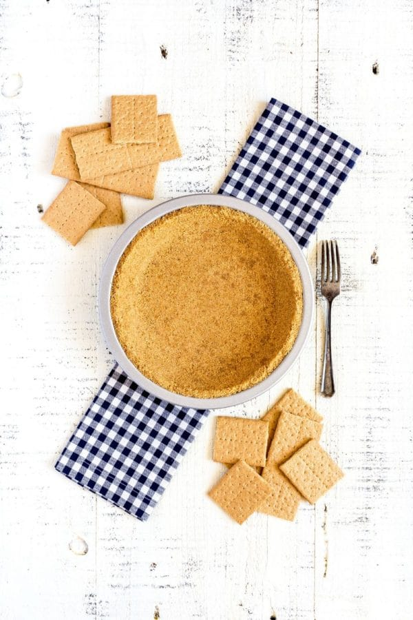 Homemade graham cracker crust on a white rustic table next to graham cracker cookies.