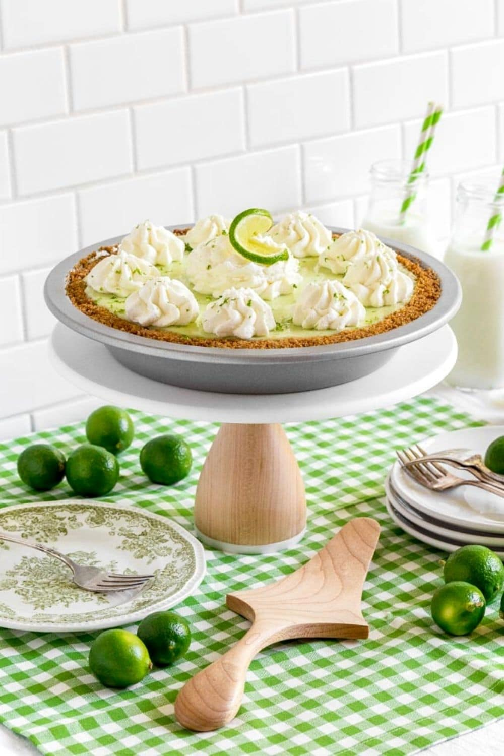 Grandma's favorite key lime pie served on a wooden cake stand next to dessert plates and forks.