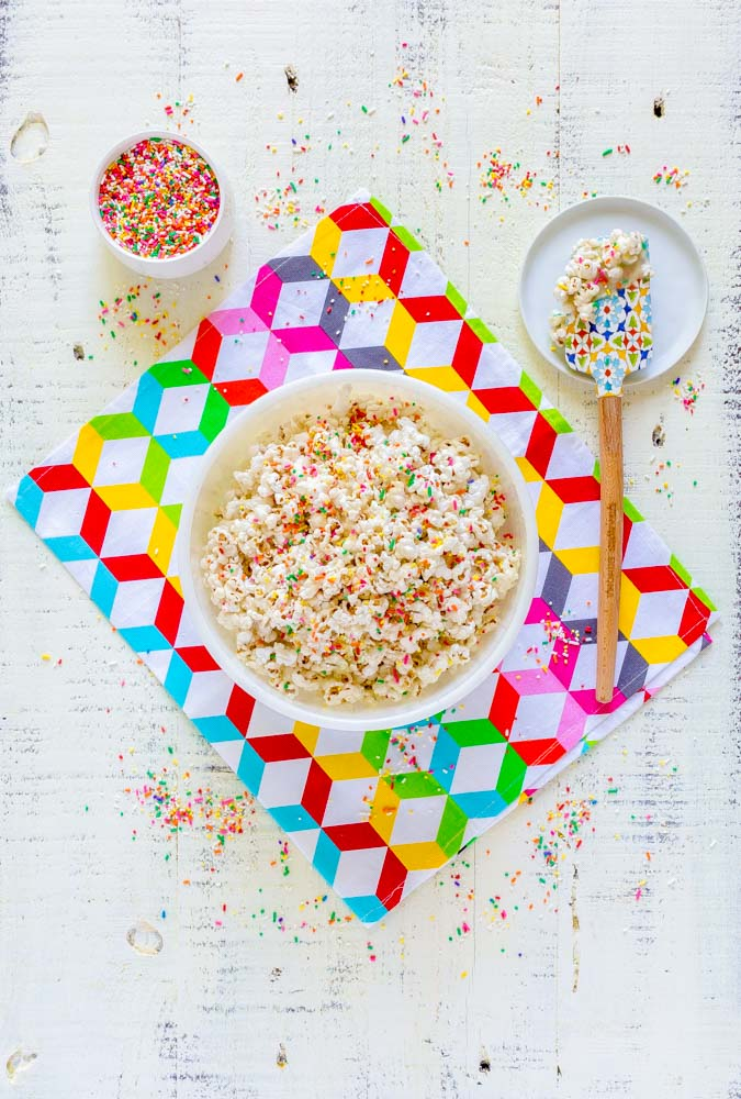Confetti popcorn in a white bowl on a colorful cloth napkin next to a tiny dish of confetti sprinkles.