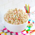 Birthday Cake Popcorn in a white bowl next to bright colorful birthday candles.
