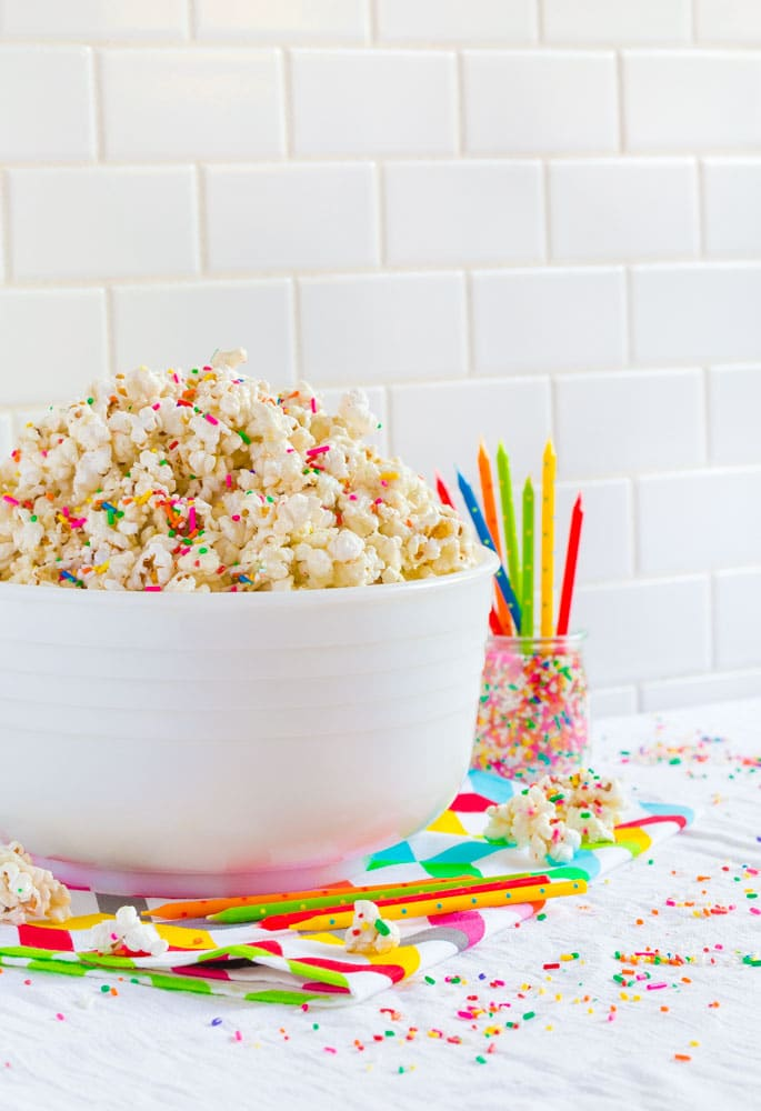 A large white serving bowl filled with birthday cake popcorn on a party table.