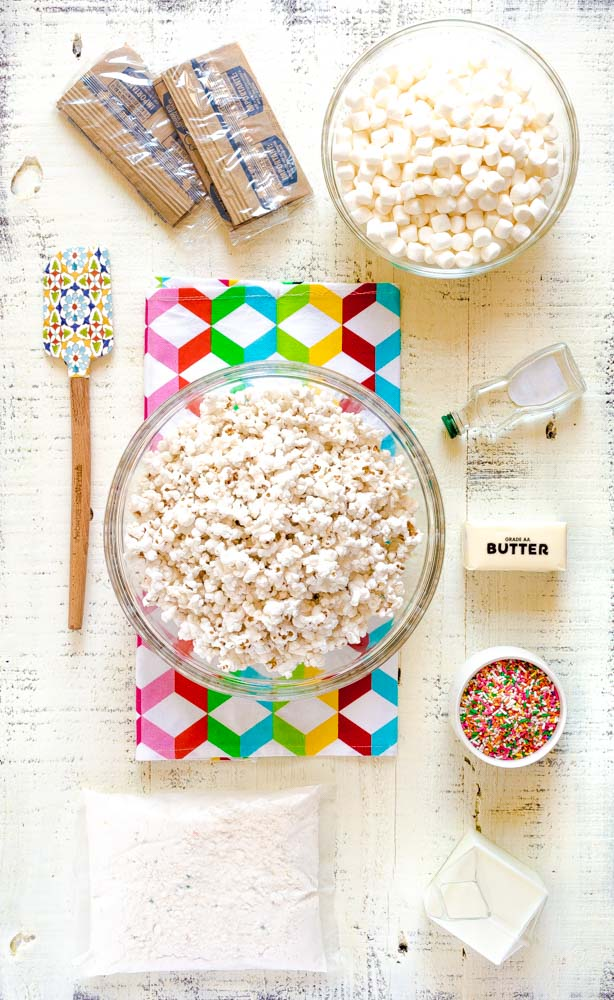 Ingredients for Birthday Cake Popcorn laid out on a rustic white tabletop.