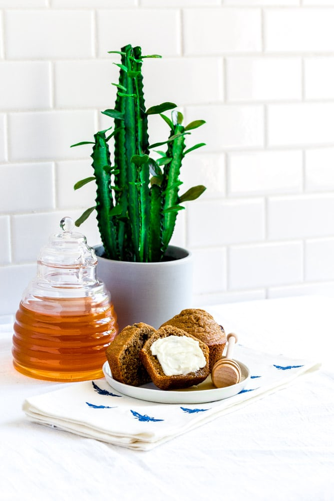 Baked goods on a small plate with honey and butter.