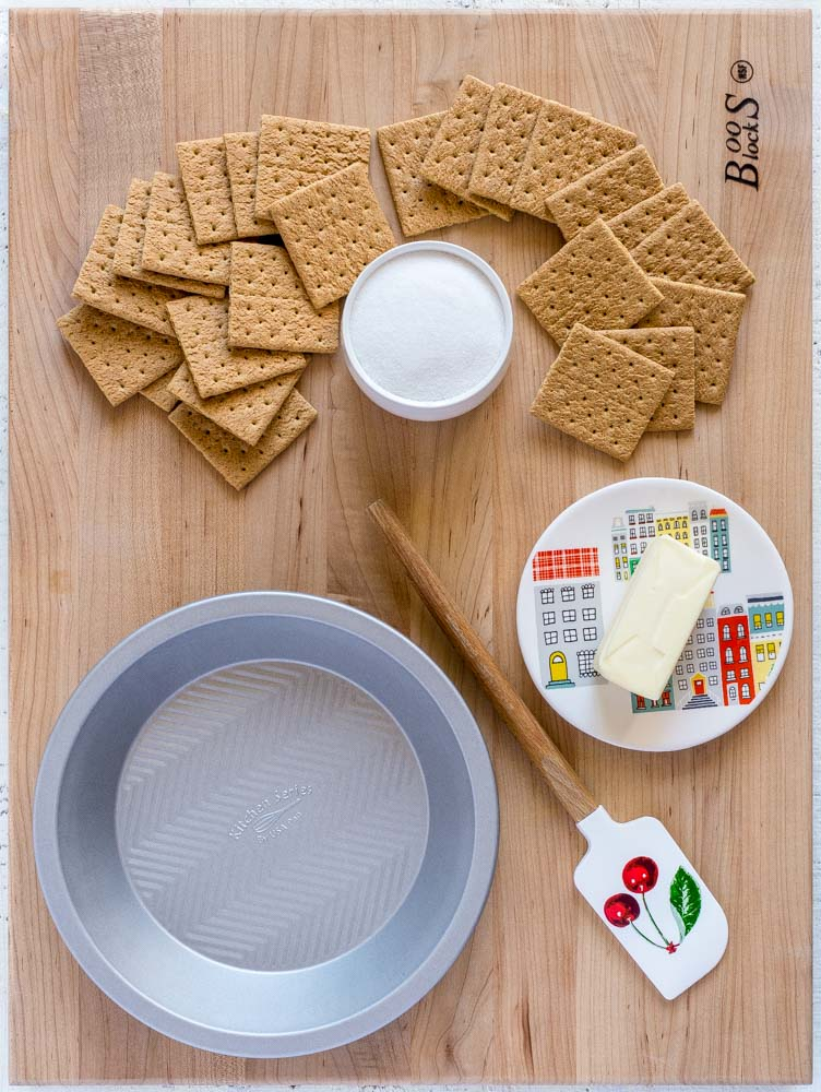 Ingredients for a graham cracker pie crust, along with a metal pie pan and rubber spatula.
