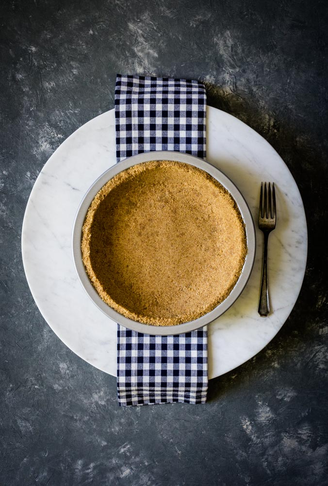 Pie crust in a metal pie plate on a round marble surface.