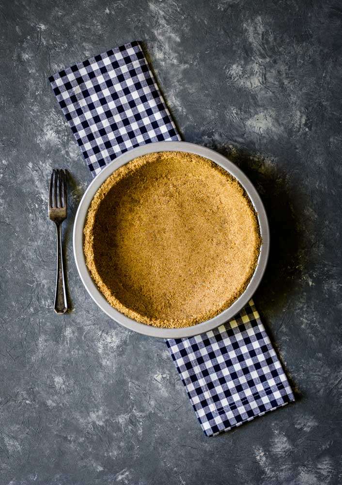 Graham cracker pie crust on a blue/white gingham cloth next to a metal fork.