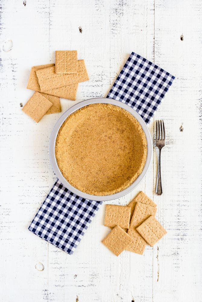 Homemade graham cracker pie crust in a metal pan next to graham crackers and a fork.