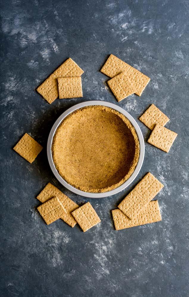 Homemade graham cracker crust in a metal pie pan next to a metal fork.
