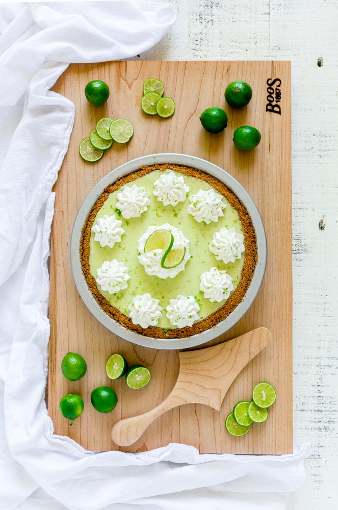 A beautiful Key lime pie on a wooden surface with a pie server.