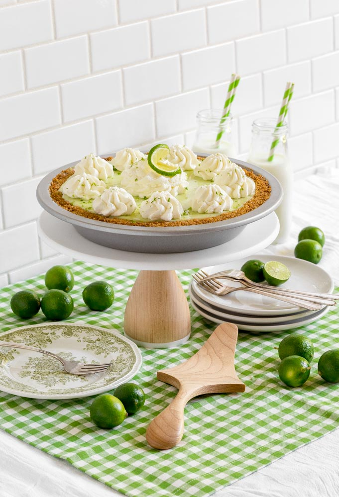 A homemade key lime pie in a metal plate garnished with piped-on whipped cream and a twisted slice of lime.