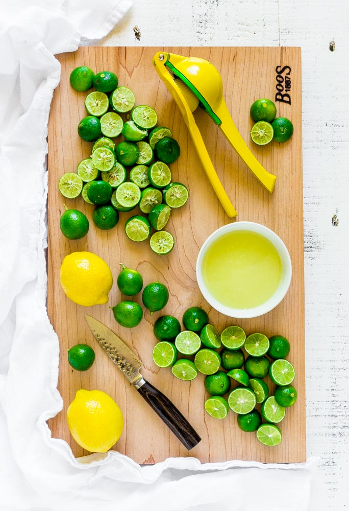 Lemons and limes being cut then squeezed with a citrus press on a wooden surface.