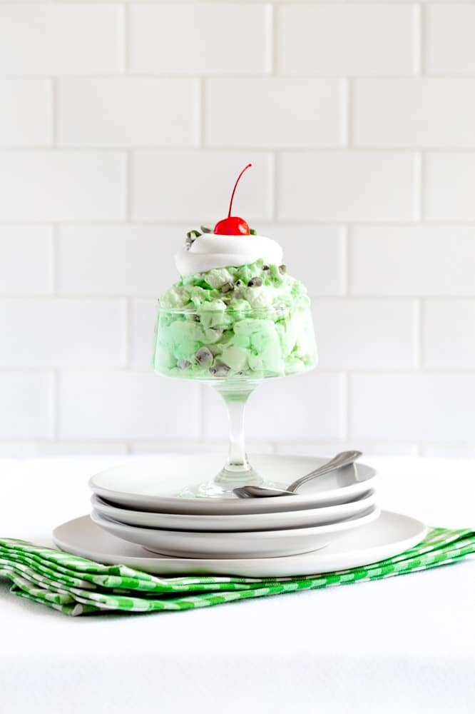 Stemmed dessert dish filled with Pistachio Fluff Watergate Salad with whipped cream and cherry.