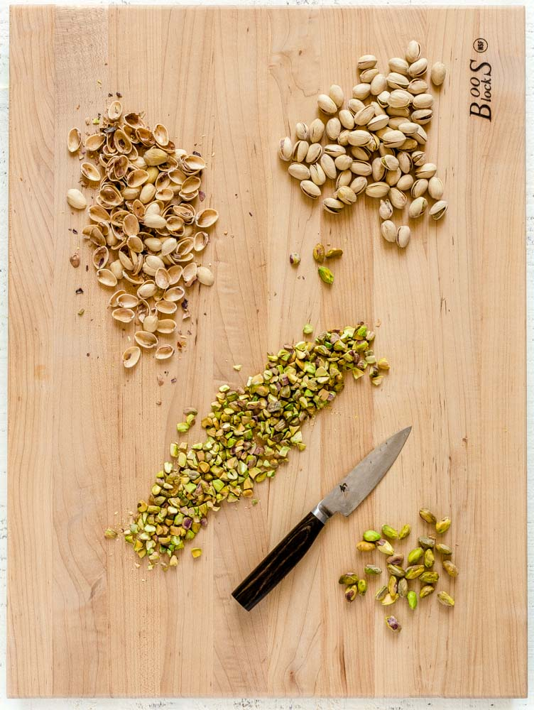 Pistachios being shelled and chopped on a wooden board with a Shun knife.