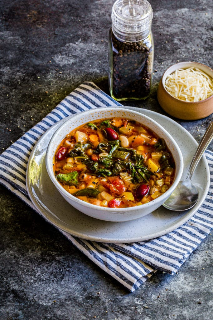 A serving of copycat Olive Garden Minestrone soup garnished with freshly-ground pepper.