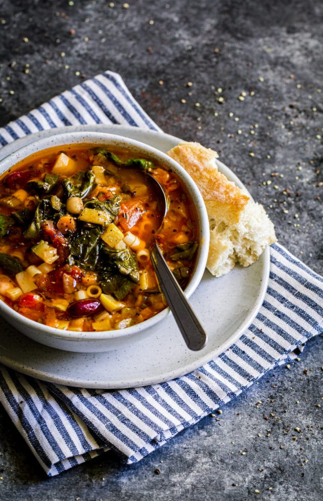 Olive Garden Minestrone Soup served in a rustic bowl with a soup spoon and artisan bread.