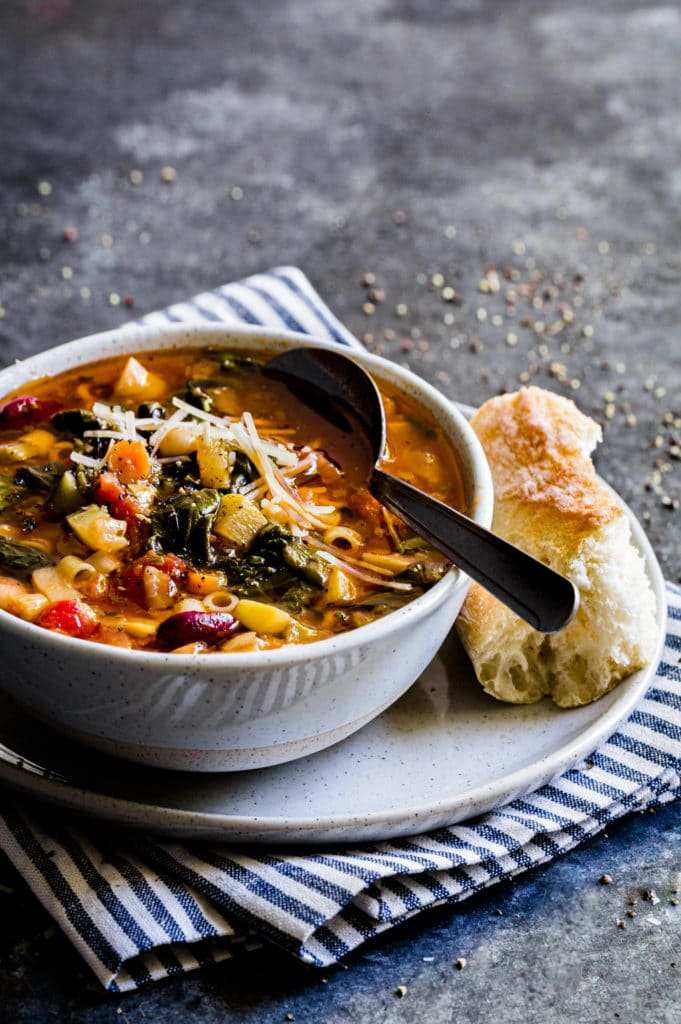 A serving of minestrone soup in a rustic bowl with a piece of fresh artisan bread.
