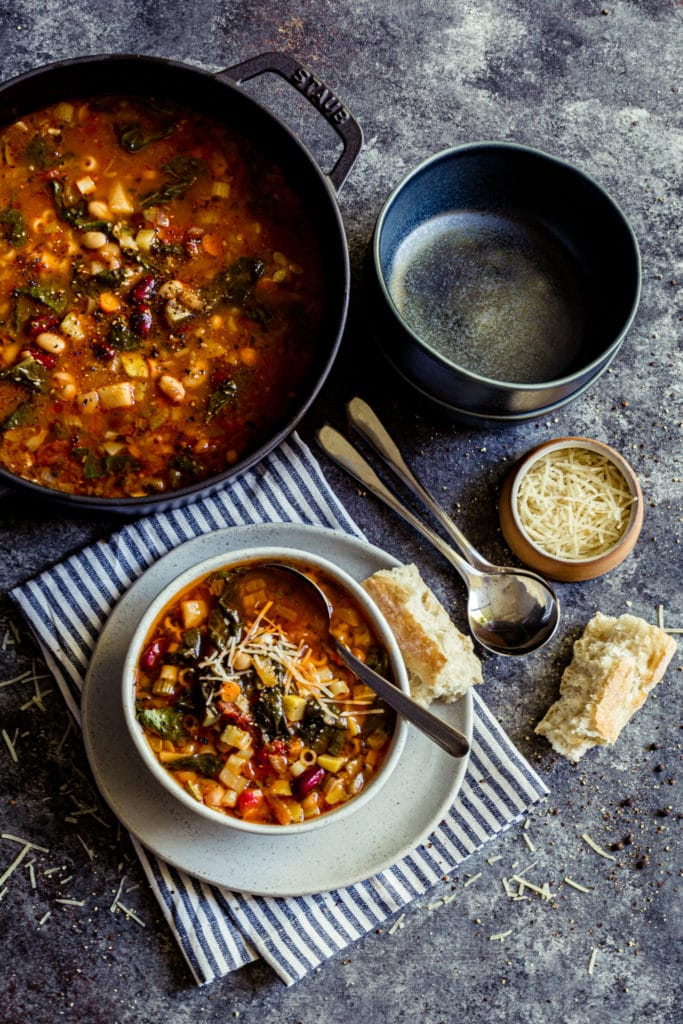 Pot of Minestrone Soup on a dinner table with a bowl of soup and bread.