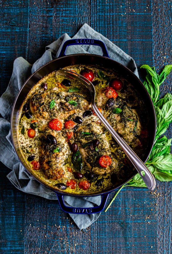 Pesto chicken in a Staub universal pan on a  deep-blue, rustic serving table.
