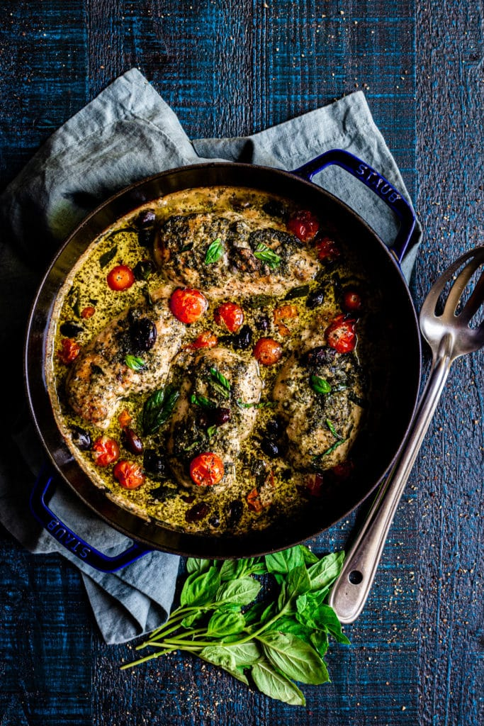 Pesto chicken bake in a cast-iron skillet with a silver serving spoon and basil leaves.