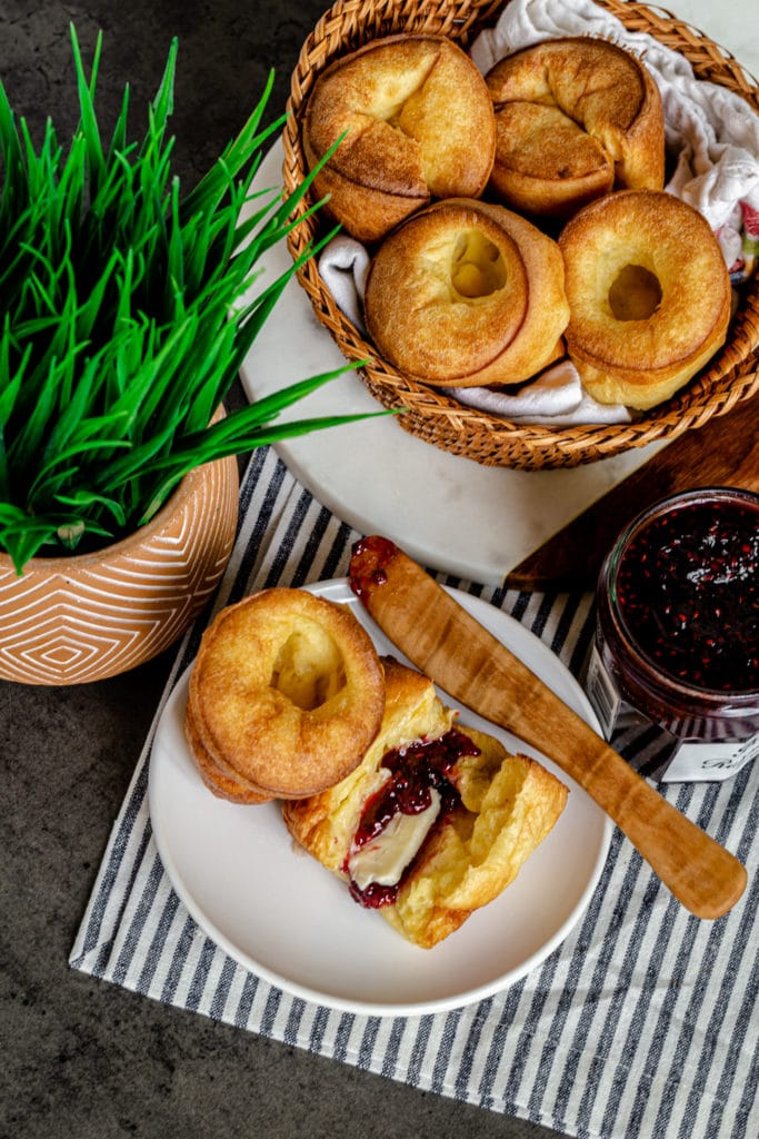 A basket of popovers next to a small plate with 2 popovers with butter and jam.
