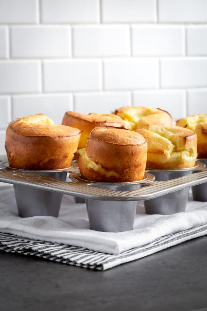 A close-up image of tall, golden, freshly-baked popovers inside a specialty popover pan.