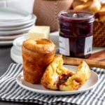 Two popovers on a small plate, with one sliced open and smeared with raspberry jam.