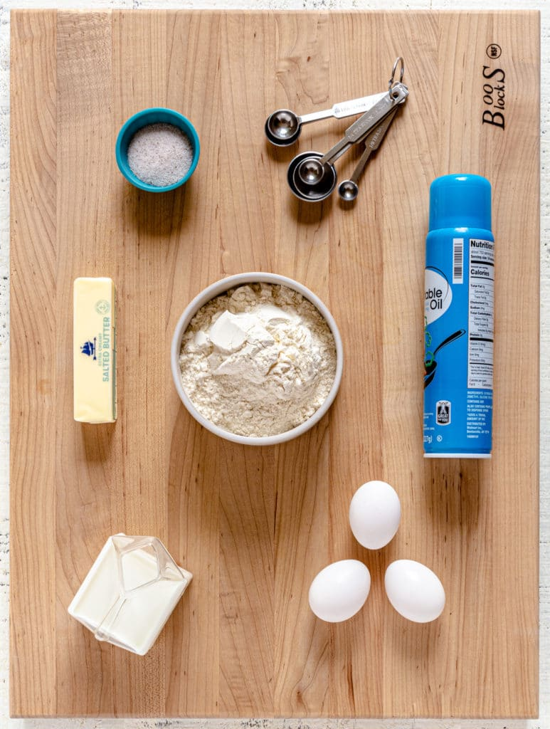Ingredients for making popovers laid out on a large wooden cutting board.