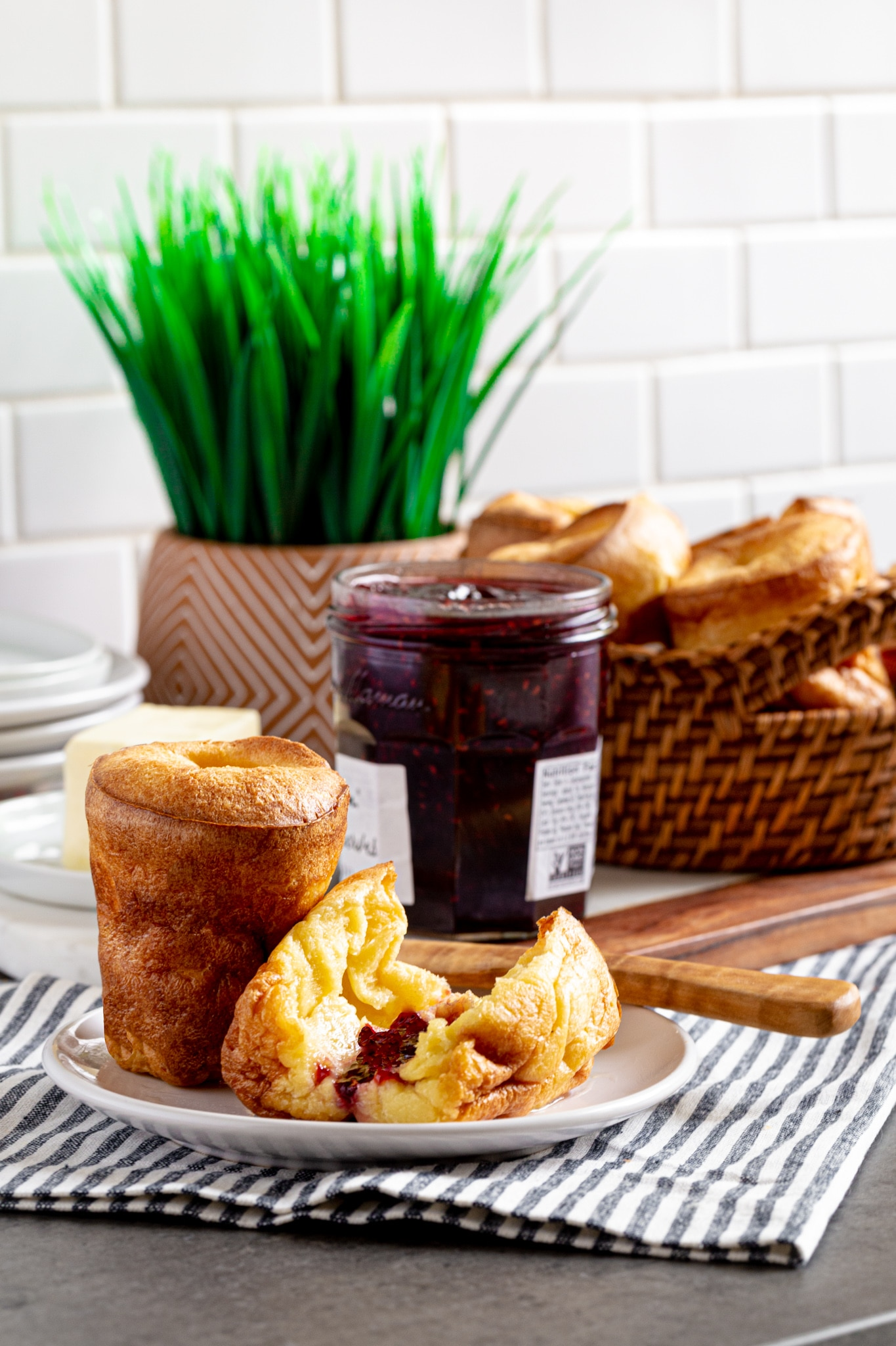 Two popovers on a plate next to a jar of jam an wicker basket with popovers.