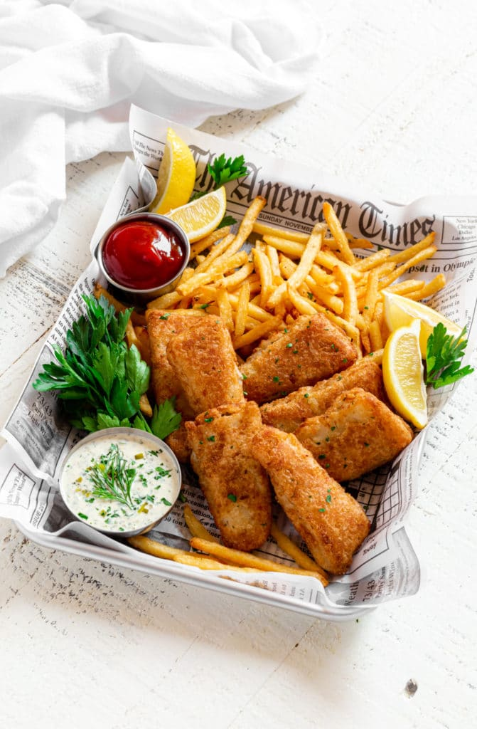 Fish and chips served on a metal tray with tartar sauce, ketchup and lemon slices.