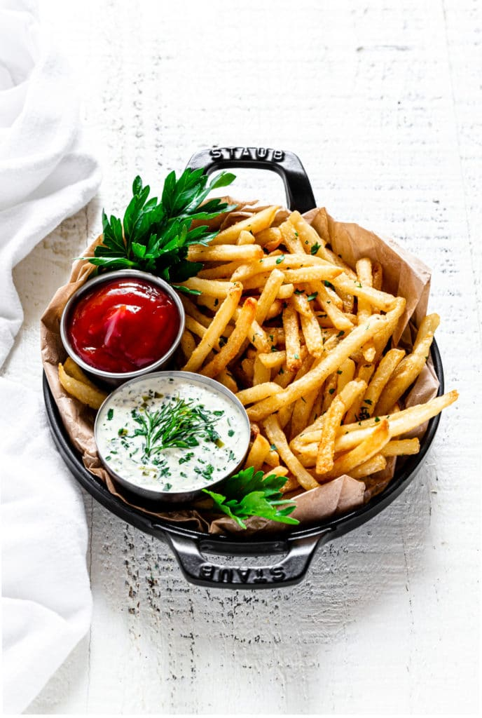 French fries served in a small Staub baker with tartar sauce and ketchup.