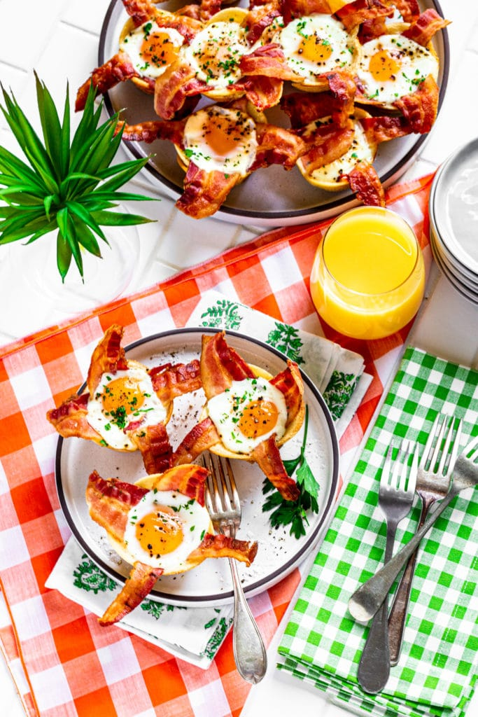 Platter of bacon egg cups on table next to 3 muffin tin eggs on a plate.